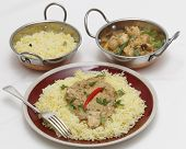 High angle view of balti chicken pasanda curry served on a bed of saffron rice, garnished with coriander leaves and a red chilli. This curry is made with yoghurt , cream and chopped coriander