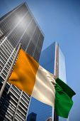 Ivory coast national flag against low angle view of skyscrapers