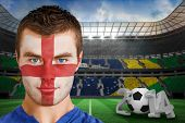 Composite image of serious young england fan with facepaint against large football stadium with fans