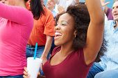 Woman In Crowd Celebrating At Sports Event