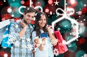 Couple with shopping bags and credit card against blurred christmas background