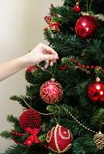girl hanging decorative toy ball on Christmas tree branch