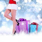 Festive womans legs in high heels against white glowing dots on blue