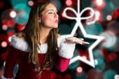 Sexy santa girl blowing a kiss against blurred christmas background