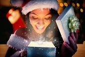 Sexy santa girl opening gift against desk with christmas tree in background