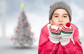 Wrapped up little girl blowing over hands against blurry christmas tree in room