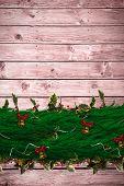 Fir branch christmas decoration garland against wooden planks background