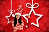 Woman pointing in the air against blurred christmas background