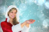 Pretty santa girl holding hands out against blurred christmas background