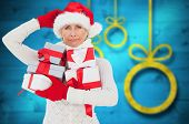 Festive woman holding gifts against blurred christmas background