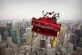 Santa flying his sleigh against city skyline
