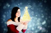 Pretty girl in santa outfit with hands out against blue abstract light spot design