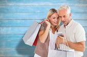 Happy couple with shopping bags and smartphone against blurred wooden planks