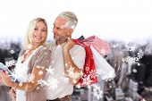 Happy couple with shopping bags and tablet pc against high angle view of city