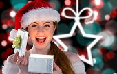 Sexy girl in santa costume opening a gift against blurred christmas background