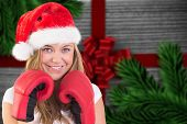 Festive blonde with boxing gloves against festive bow over wood