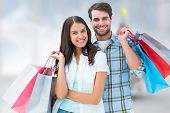 Happy couple with shopping bags against blurry christmas tree in room