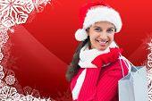 Festive brunette holding shopping bag against christmas themed snow flake frame