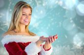 Pretty girl holding hands out in santa outfit against blurred christmas background