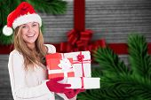 Festive blonde holding pile of gifts against festive bow over wood