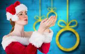 Pretty girl in santa costume holding hand out against blurred christmas background