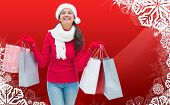 Festive brunette holding shopping bags against christmas themed snow flake frame