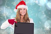 Festive blonde pointing to laptop against blurred christmas background