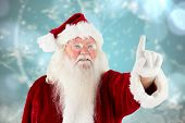 Santa claus pointing against blurred christmas background