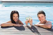 Portrait of a young couple toasting champagne in swimming pool on a sunny day