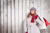 Happy blonde in winter clothes posing against blurred wooden planks