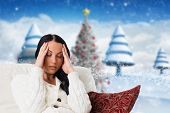 Woman suffering from a migraine against blurry christmas scene