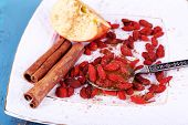 Ripe apple, honey in spoon, goji berries  and cinnamon on white square plate on blue wooden background
