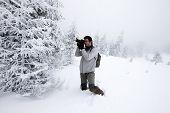 Photographer in foggy winter landscape