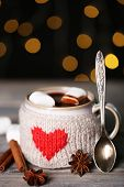 Cup of tasty hot cocoa, on wooden table, on shiny background