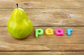 Pear word formed with colorful letters on wooden background