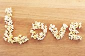 Love word formed with popcorn on wooden table