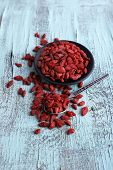 Goji berries in black saucer and metal spoon on blue wooden background