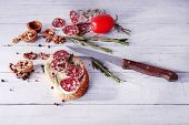 Sandwich with salami, rosemary and walnuts on wooden background