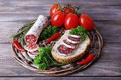 French salami with tomatoes, bread and parsley on wicker mat on wooden background
