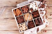 Wooden box with set of coffee and cocoa beans, sugar cubes, dark chocolate, cinnamon and anise, close-up, on wooden background