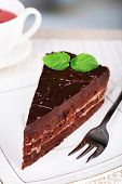 Piece of chocolate cake on plate and cup of tea on wooden table on natural background