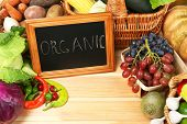 Fresh organic vegetables with chalkboard on wooden table, close up