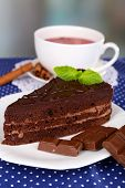 Piece of chocolate cake on plate and cup of tea on polka dot tablecloth on natural background