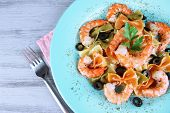 Fresh prawns with coloured macaroni, olives and parsley in a big blue round plate with a fork on wooden background