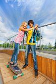 Boy holds hands of girl, teaches riding skateboard