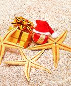 Christmas Bauble, Starfishes And A Gift Box On  Sand