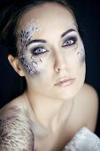 fashion portrait of pretty young woman with creative make up like a snake, victim with python skin c