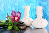 Spa composition with herbal massage bags, orchid and bamboo on table on blue background