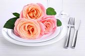 Table setting with pink rose on plate