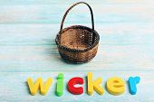 Wicker word formed with colorful letters on wooden background